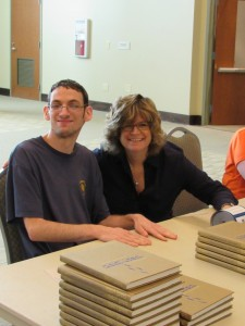 Bunzl Family Cantorial Chair Beth Schafer sits with one of the workers supplied by Jewish Family & Career Services to unpack and label the new mahzors.