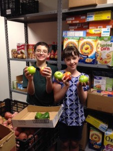 Bar mitzvah Andrew Krause and sister Stephanie stock the shelves at the JF&CS Kosher Food Pantry.