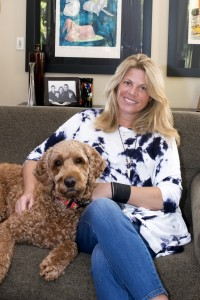 Robin Brill and goldendoodle JoJo enjoy furniture by Mitchell Gold and Isamu Moguchi in front of the Israeli Menashe Kadishman's animal painting.