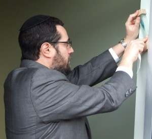 Rabbi Joshua Heller places the mezuzah on the MACoM doorway.