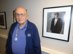 "Eli West Jacobs stands by his portrait in the ""American Heroes: Portraits of Service"" display at Belmont Village. (Photo by Kevin Madigan)"