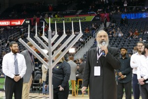 Rabbi Yossi New addresses the crowd at Philips Arena before the menorah lighting on the seventh night of Chanukah.
