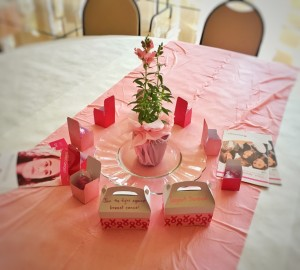 A table is set with information for Shearith Israel's recent Sharsheret Pink Shabbat.