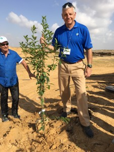 Alan Lubel plants a tree in the Halutza community, where JNF honoree Yedidya Harush offered a helping hand.
