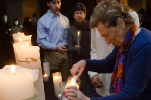 Holocaust survivors, including keynote speaker Thomas Buergenthal, take turns lighting candles during the ceremony before Buergenthal's speech.