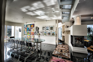 "Lynette Joel's ""Twelve Tribes,"" son David's charcoal of Martin Luther King Jr. and son Jared's ""Seven Days of Creation"" fill the wall behind the Freundt aluminum table in the dining room."