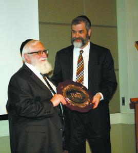 Rabbi Ilan Feldman congratulates Rabbi Daniel Estreicher after presenting him a challah board as part of the community's gift.
