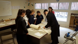 Rabbi Mordechai Danneman shows Chaya Mushka middle school girls how a Torah is put together.