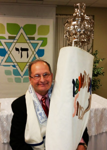 Rabbi Ronald Gerson holds Congregation Chai's first Torah.