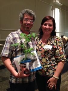 Jason and Sandrine Simmons prepare to leave with their MAZON tzedakah box tomato plant and haggadah.