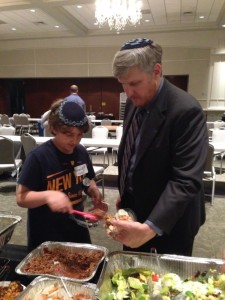 Rabbi Laurence Rosenthal and son Avram Eli prepare meals for the needy with the seder leftovers.