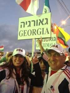 Kenny Silverboard and fellow Atlantan Megan Light take a photo with the sign for the delegation from the former Soviet republic of Georgia at the opening ceremonies at Teddy Stadium in Jerusalem in 2013. Light competed in open women's softball and won a gold medal with Team USA.