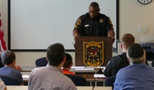 Beth Jacob congregants join DeKalb police in listening to Sgt. D.J. Brown make roll-call announcements July 20.