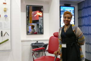 Exhibit curator Calinda Lee stands inside Eli Sotto's re-created barbershop.