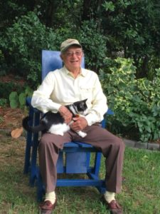 """Joel Adler sits with his cat, Oreo, in a custom-made chair by Walt Meyers. Adler says, """"Every garden needs a cat."""""""