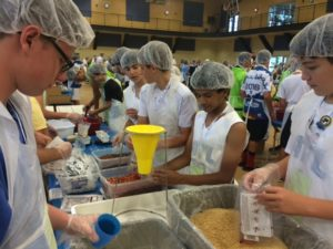Members of the boys 14U basketball team pack meals for the St. Louis Are Foodbank as part of the community service component at the games.