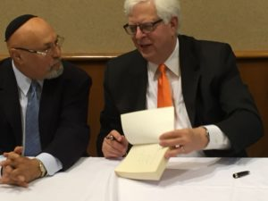 Dennis Prager signs one of his books while talking with Arthur Kurtz.