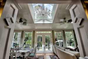A sparkling Waterford chandelier accents the casual pastel sun room and skylight