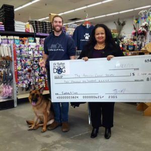 Doug Ratner and German shepherd Oggy present a $2,100 check to the American Cancer Society to fight canine cancer.