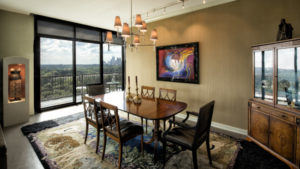 The Nemo dining room features the table and china cabinet from Carol's childhood home. The Peter Max painting, purchased at a charity auction, adds a pop of color to the Atlanta skyline.