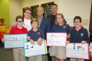 Davis Academy seventh-graders (from left) Jason Sherman, Danny Kobrinsky, Asher Bressler, Jenny Sullivan and Matthew McCullough present letters of appreciation from first-graders to Sandy Springs Police Chief Kenneth DeSimone and Capt. John Mullin during the GILEE visit to the academy Nov. 7.