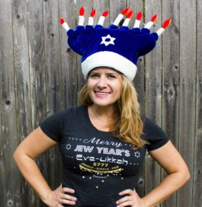 Amy Kritzer, who says owning ModernTribe has been a lot of fun, shows some jingle, sizzle and pop with the Merry Jew Year's Eve-ukkah T-shirt ($36) and a menorah hat ($25).