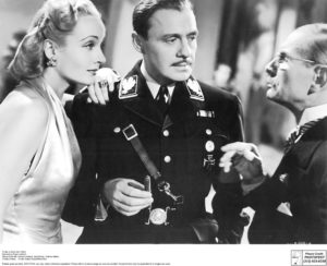 "Carole Lombard, Jack Benny (center) and Charles Halton plot stage success and Nazi embarrassment in ""To Be or Not to Be."""