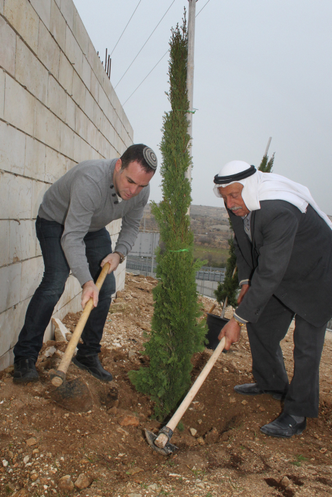The mayor of the settlement of Efrat, Oded Revivi (L), and mukhtar of the Palestinian village George, Abu Taleb, plant  a tree in honor of Tu B'Shvat (photo credit: Gershon Elinson/Flash90)