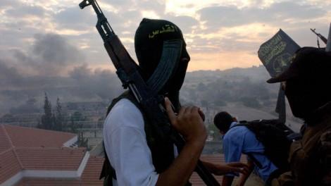 Hamas gunmen survey the smoldering ruins of a Gush Katif settlement after the 2005 disengagement (file photo credit: Flash90)