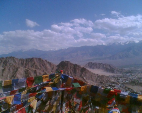 Tibetan Buddhist prayer flags flutter at Tsemo Fort above Leh, with the snow-clad peaks of the Indian Himalaya in the distance (photo credit: Gavin Gross)