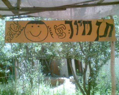 Sign in the courtyard of Habayit Hayehudi: 'Give a smile, everything is for the best.' (photo credit: Gavin Gross)