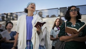 The author (left, wearing a purple shirt) prays at the Western Wall with other women on Wednesday (photo credit: Miriam Alster/Flash90)