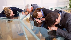 businessman and businesswoman exhausted during a meeting