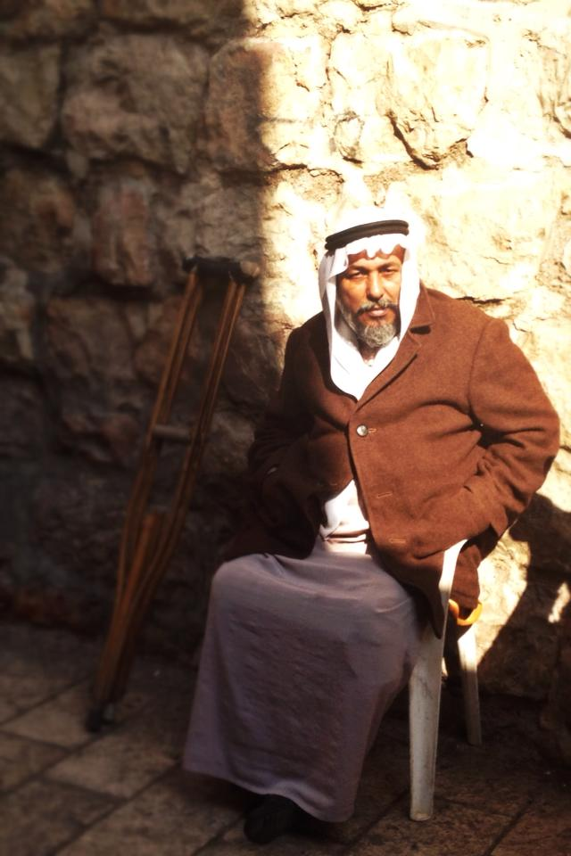 A man sits in the Muslim Quarter of the Old City. Photo by Sarah Tuttle-Singer