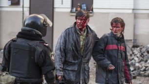 Wounded people are seen after clashes with riot police in central Kiev