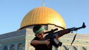 A Palestinian child wears a Hamas headband and aims a toy gun during a rally to support of Gaza, after Eid prayers at the Al-Aqsa Mosque, in Jerusalem's Old City, on July 28, 2014. (Photo: Sliman Khader/Flash90)
