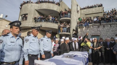 Police officers stand next to the coffin of Israeli police officer Zidan Saif