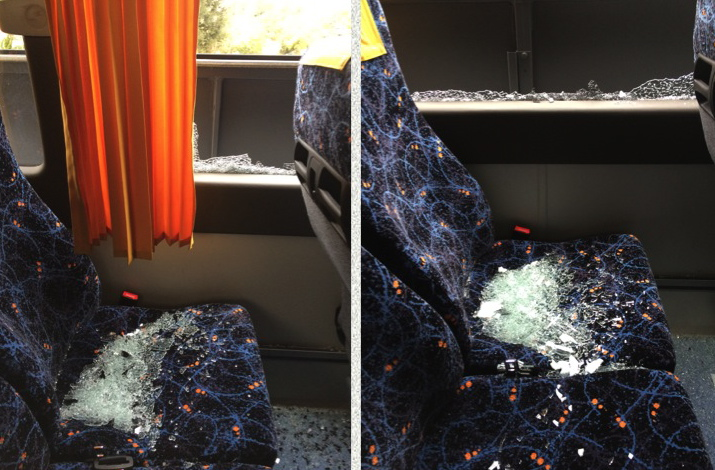 The tour bus was soon covered in broken glass.