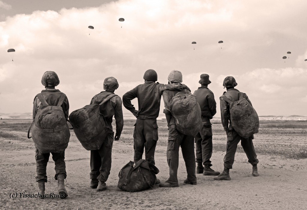 Paratroopers watching their fellow soldiers jump safely