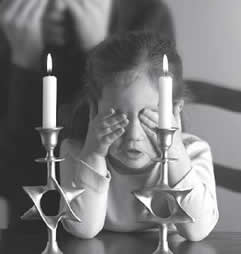 child blessing shabbat candles