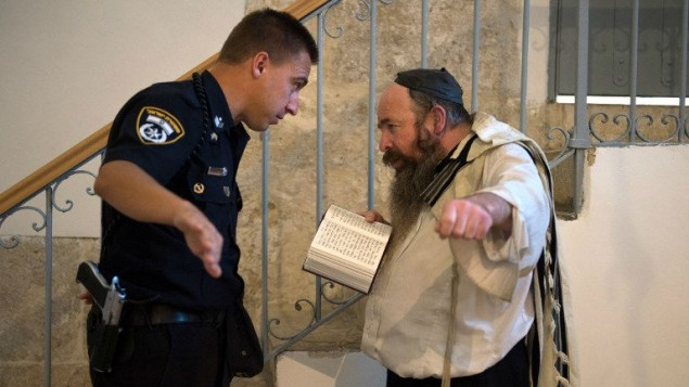 An Israeli policeman asks a Jewish man reciting the Psalm of David to leave the Cenacle or Upper Room on Mount Zion just outside the Old City of Jerusalem, on May 21, 2014. The site, on the itinerary of Pope Francis's visit to the Holy Land, is also considered holy to Jews and Muslims. (photo credit: AFP/ CONSTANCE DECORDE)