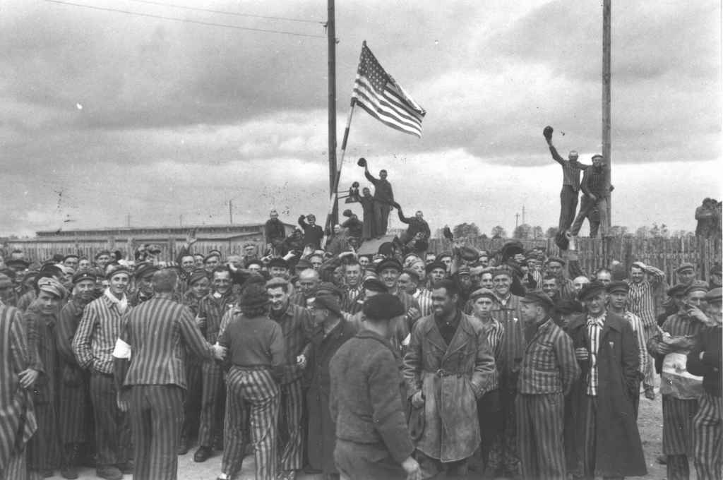 Dachau, Germany, Prisoners of the concentration camp raise the American flag after the liberation. (Photo: courtesy Yad Vashem Archives)