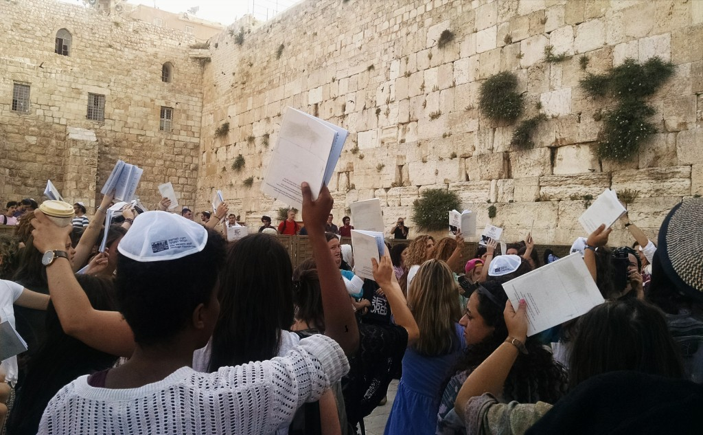 Women of the Wall hold their siddurim in the air during prayer