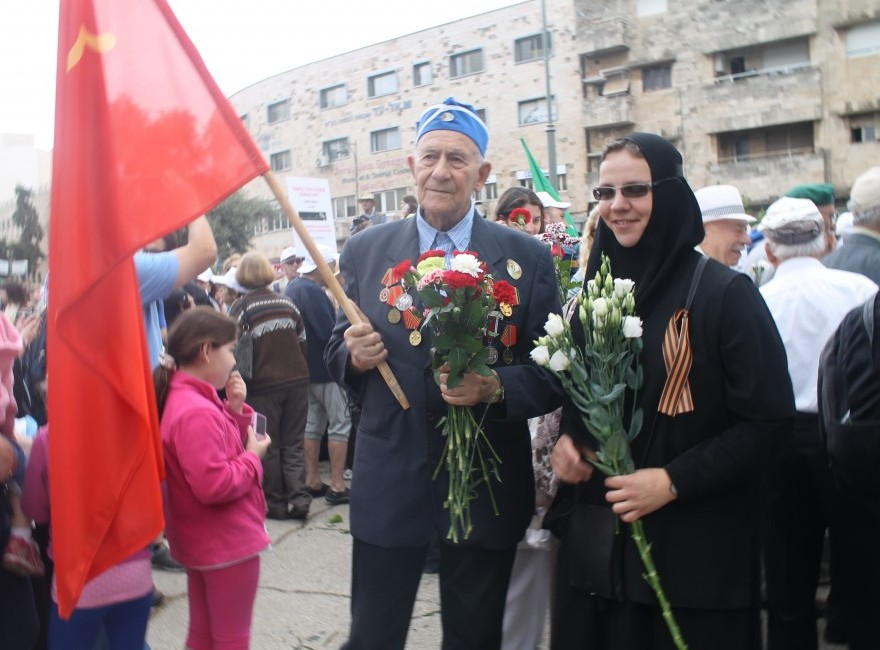 A veteran carrying the hammer and sickle flag, standing by a nun from the Russian Orthodox Church