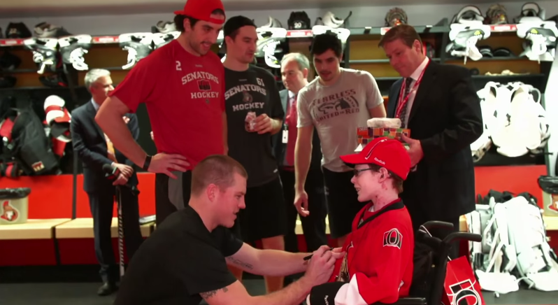 In the locker room, surrounded by players from the NHL's Ottawa Senators.