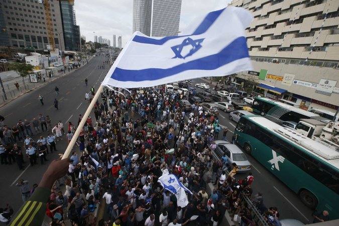 An Ethiopian-Israeli protester waves the Israeli flag. Credit: New York Times