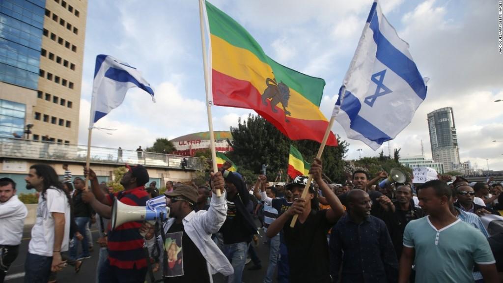 Ethiopian-Israeli protesters wave the Ethiopian and Israeli flags. Credit: CNN
