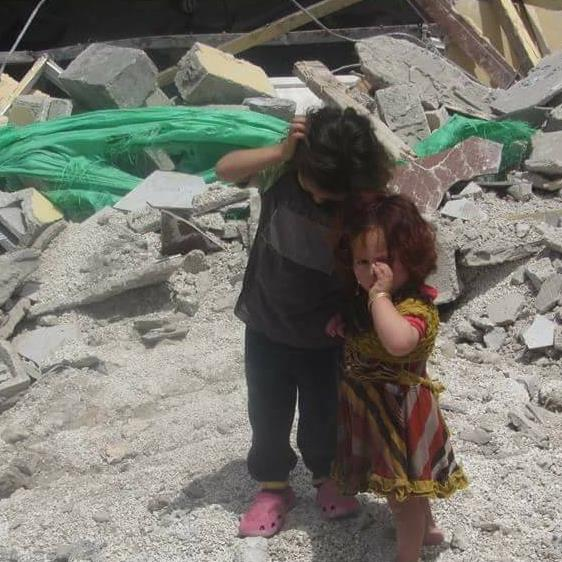 Children in front of their demolished home.