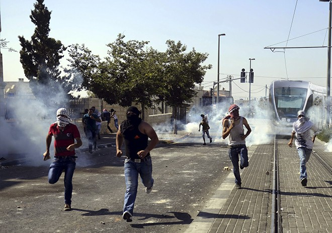Arab rioters flee a cloud of teargas from the train's grenade launchers, visible to the left and right of the driver's window.