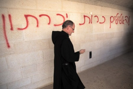 "A priest walks past a graffiti reading in Hebrew ""idols will be cast out"" as he inspects the damage at the Church of the Multiplication at Tabgha, on the shores on the Sea of Galilee in northern Israel, on June 18, 2015 AFP PHOTO / MENAHEM KAHANA"
